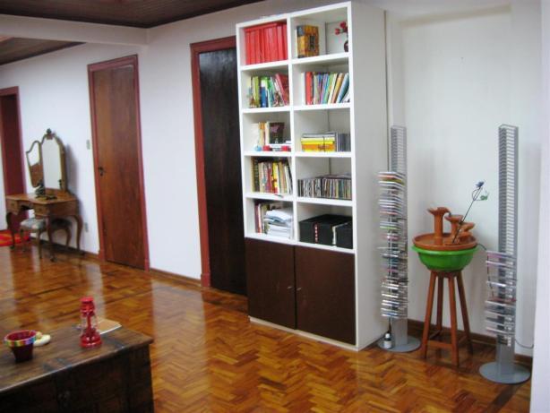 A esquerda da estante está a porta indesejável. E a direita da estante o lugar onde foi aberto o vão de passagem.